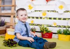 Ragazzo che si siede con un mazzo dei fiori in un vestito del denim Fotografia Stock Libera da Diritti