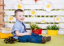 Ragazzo che si siede con un mazzo dei fiori in un vestito del denim Fotografie Stock
