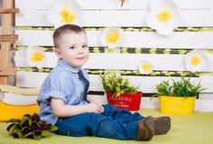 Ragazzo che si siede con un mazzo dei fiori in un vestito del denim Fotografie Stock Libere da Diritti