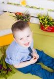 Ragazzo che si siede con un mazzo dei fiori in un vestito del denim Fotografia Stock