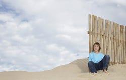 Ragazzo che si siede contro il recinto di legno On Sandy Beach Fotografia Stock Libera da Diritti