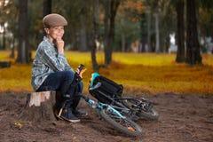Ragazzo che si siede nel parco con la sua bicicletta sul pavimento fotografie stock libere da diritti