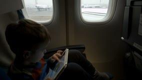 Ragazzo che si siede nell'aereo e che per mezzo del PC della compressa archivi video