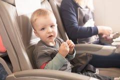 Ragazzo che si siede nella sedia dell'aeroplano Immagine Stock