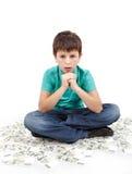 Ragazzo che si siede sui soldi Fotografia Stock