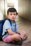 Ragazzo che si siede sul corridoio a scuola Fotografie Stock