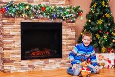 Ragazzo che si siede sul pavimento vicino all'albero di Natale Fotografia Stock Libera da Diritti