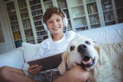 Ragazzo che si siede sul sofà con il cane di animale domestico e che ascolta la musica sulla compressa digitale fotografie stock libere da diritti