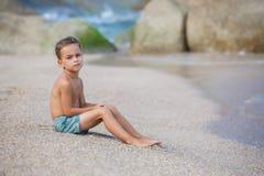 Ragazzo che si siede sulla sabbia dal mare fotografia stock