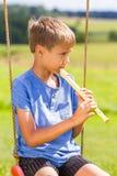Ragazzo che si siede sulle oscillazioni e che gioca flauto all'aperto immagine stock