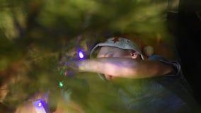 Ragazzo che si trova sotto l'albero di Natale ed appendere le decorazioni di Natale video d archivio