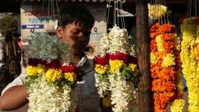 Ragazzo che sistema le decorazioni ad un supporto della via in Goa video d archivio