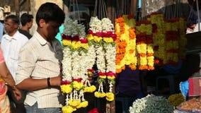 Ragazzo che sistema le decorazioni ad un supporto della via in Goa stock footage