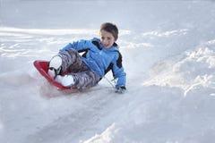 Ragazzo che sledding giù una collina nella neve fotografia stock