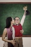 Ragazzo che solleva bacio del trofeo tramite la sua madre nel codice categoria Immagini Stock Libere da Diritti