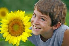 Ragazzo che sorride con un fiore Fotografia Stock Libera da Diritti