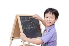 Ragazzo che sorride fra la risposta di per la matematica di scrittura Fotografia Stock