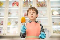 Ragazzo che sta alla cucina con la lecca-lecca Fotografie Stock Libere da Diritti