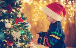 Ragazzo che sta l'albero di Natale vicino Fotografia Stock