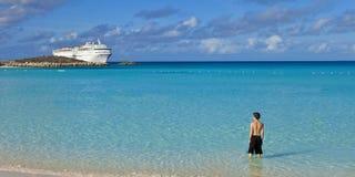 Ragazzo che sta sulla spiaggia tropicale con la nave da crociera Fotografie Stock Libere da Diritti
