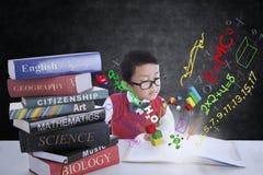 Ragazzo che studia con i libri e la formula Fotografia Stock
