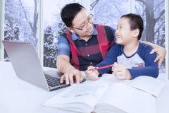 Ragazzo che studia e che parla con il papà a casa Fotografie Stock