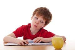 Ragazzo che studia e distratto con una mela Fotografia Stock