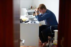 Ragazzo che studia nella camera da letto facendo uso del computer portatile Immagini Stock