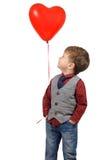 Ragazzo che tiene il pallone a forma di del cuore rosso Fotografie Stock
