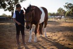 Ragazzo che tiene le redini di un cavallo nel ranch Immagini Stock