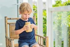 Ragazzo che tiene un frullato della banana, concetto adeguato di nutrizione Immagine Stock