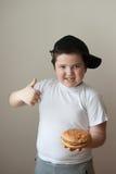 Ragazzo che tiene un hamburger e gli aumenti il suo pollice su Immagini Stock Libere da Diritti