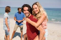 Ragazzo che trasporta sulle spalle amica dagli amici alla spiaggia Fotografie Stock Libere da Diritti