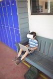 Ragazzo che usando i vetri di realtà virtuale e del computer portatile mentre sedendosi sul banco Fotografia Stock Libera da Diritti