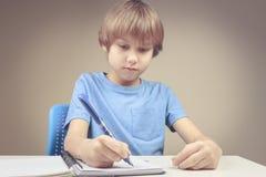 Ragazzo che usando penna e scrivendo sul taccuino di carta a spirale Ragazzo che fa i suoi esercizi di compito Immagini Stock Libere da Diritti