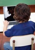 Ragazzo che utilizza computer portatile nell'asilo Fotografia Stock Libera da Diritti
