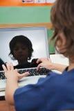 Ragazzo che utilizza computer portatile nell'aula Fotografia Stock