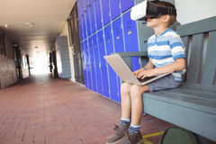 Ragazzo che utilizza i vetri di realtà virtuale e del computer portatile mentre sedendosi sul banco nel corridoio Fotografia Stock