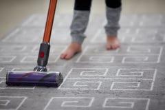 Ragazzo che utilizza un aspirapolvere mentre pulendo tappeto nella casa immagini stock