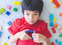 Ragazzo circondato dalle finestre aperte variopinte di vista superiore dei blocchetti del giocattolo al cuore immagine stock libera da diritti
