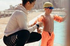 Ragazzo a classe di nuoto con l'istruttore fotografie stock libere da diritti