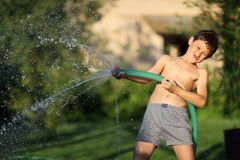 Ragazzo con acqua della spruzzata nel giorno di estate caldo Fotografie Stock Libere da Diritti