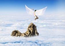 Ragazzo con Angel Wings che vola intorno nel cielo Fotografie Stock