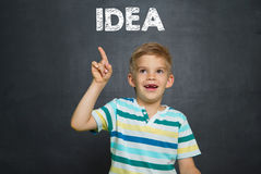 Ragazzo con gesso e consiglio scolastico con l'IDEA del testo Immagini Stock