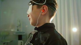 Ragazzo con gli elettrodi sulla testa che guarda al monitor - sistema diagnostico del ` s dei bambini di sanità - ricerca in ofta video d archivio