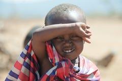 Ragazzo con gli occhi pieni delle mosche, Tanzania di Maasai Le mosche fanno le uova negli occhi in modo che il bambino abbia pot fotografia stock libera da diritti