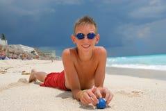 Ragazzo con gli occhiali di protezione sulla spiaggia Fotografie Stock
