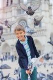Ragazzo con gli uccelli vicino alla cattedrale di Notre Dame de Paris a Parigi, Francia Immagini Stock Libere da Diritti