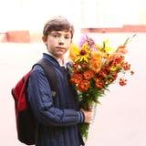 Ragazzo con i fiori al primi del giorno di scuola di settembre Fotografia Stock Libera da Diritti