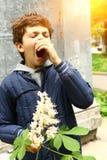 Ragazzo con i fiori della castagna che starnutisce dall'allergia Fotografia Stock